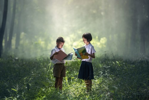 Boy and girl studying in forest